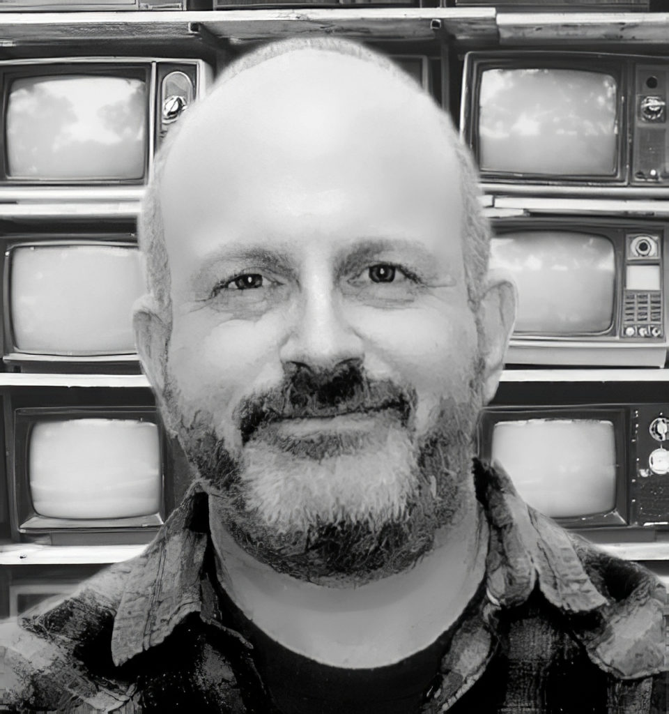 The author in front of a wall of 20th-century televisions